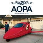 A Switchblade in a driveway facing the road with Sam Bousfield standing next to it, above is a logo of the AOPA